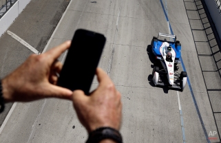 Brad Scott takes pictures as Jean-Eric Vergne, of France, competes in a qualifying session of the Formula E Long Beach ePrix auto race, Saturday, April 4, 2015, in Long Beach, Calif. (AP Photo/Jae C. Hong)