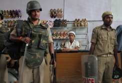 Indian policemen stand guard in front of a shoe store near Mecca Masjid in Hyderabad, India, Friday, April 10, 2015. Security was increased as a preventive measure on the first Friday following the killing of five prisoners, including one accused of terrorism, when, according to the police, they tried to escape from a police van on Tuesday. (AP Photo/Mahesh Kumar A.)