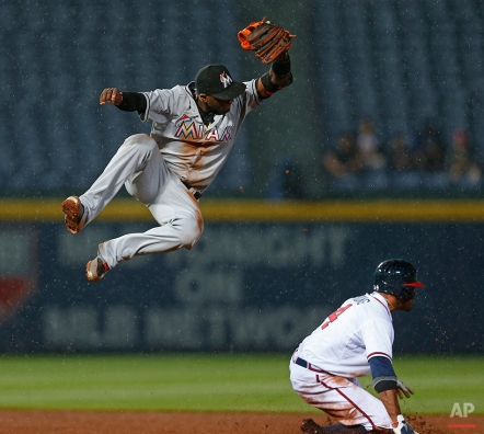 Atlanta Braves center fielder Eric Young Jr. (4) steals second base as Miami Marlins shortstop Adeiny Hechavarria (3) leaps for the wild throw in the fifth inning of a Major League baseball game Tuesday, April 14, 2015, in Atlanta. Young advanced to third. (AP Photo/John Bazemore)