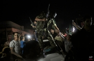 Palestinians greeting a masked militant fas they celebrate the cease-fire in Gaza City, Aug. 26, 2014. (AP Photo/Khalil Hamra)