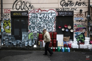 A man makes his way past various goods for sale at a market street of Athens, on Thursday, April 9, 2015. Greece's new left wing-led government has been locked in strained negotiations with creditors since winning elections in January on pledges to abolish the deeply resented budget austerity measures required by the rescue program. (AP Photo/Yorgos Karahalis)