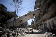 Palestinians attend Friday noon prayer beneath the fallen minaret of the Soussi mosque that was hit by Israeli strikes in Gaza City, Aug. 8, 2014. (AP Photo/Khalil Hamra)