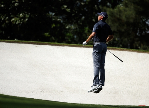 Matt Kuchar leaps to see the pin on the fifth hole during the second round of the Masters golf tournament Friday, April 10, 2015, in Augusta, Ga. (AP Photo/Charlie Riedel)