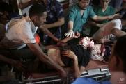 Medics wheel two wounded Palestinians into the emergency room of Shifa hospital in Gaza City, northern Gaza Strip, early Friday, July 18, 2014. (AP Photo/Khalil Hamra)