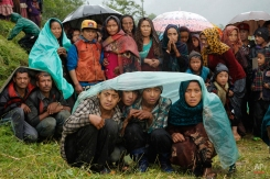 Villagers wait in the rain as an aid relief helicopter lands at their remote mountain village of Gumda, near the epicenter of Saturday's massive earthquake in the Gorkha District of Nepal, Wednesday, April 29, 2015. (AP Photo/Wally Santana)