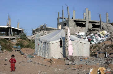 A Palestinian girl stands next to a tent where her family lives after their home was destroyed, in the Shijaiyah neighborhood of Gaza City, Monday, March 30, 2015. (AP Photo/Khalil Hamra)
