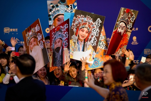 Fans wave posters depicting Chinese opera singers at the grand opening of the 5th annual Beijing International Film Festival in Beijing, Thursday, April 16, 2015. (AP Photo/Mark Schiefelbein)