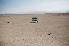 A signboard in the desert landscape indicates said property was founded by Esperanza, in Nazca, Peru, Thursday, April 16, 2015. In this desert region, owners mark their property with signboards in an attempt to prevent land traffickers or squatters from seizing their land, which in some instances will be resold by land traffickers using false documentation. (AP Photo/Rodrigo Abd)