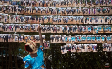 """A young mourner inspects photographs of other mourners taken by a photographer when the body was released from the mortuary earlier in the morning, for sale to mourners as a souvenir, at the funeral of 22-year-old business management student Angela Nyokabi Githakwa, who was killed in the Garissa University College attack and known to her friends as """"Jojo"""", in the village of Mutunguru, Kenya, Friday, April 10, 2015. At one of the first funerals for the students killed in the Garissa attack, dozens of her friends and relatives gathered to say their final goodbyes at a funeral service held at the St. Joseph Catholic church, followed by a burial next to the banana plot at her parent's farm. (AP Photo/Ben Curtis)"""