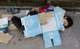 Walid Tarek, 11, uses a cardboard box to cover himself from the early morning chill in Cairo, Egypt, early Friday, April 10, 2015. (AP Photo/Amr Nabil)
