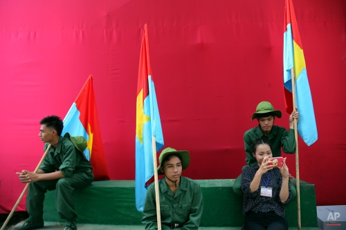 An artist takes selfie photo with others who are in military uniform and hold Vietcong flags on the backstage during a parade celebrating the 40th anniversary of the end of the Vietnam War which is also remembered as the fall of Saigon, in Ho Chi Minh City, Vietnam, Thursday, April 30, 2015. (AP Photo/Na Son Nguyen)