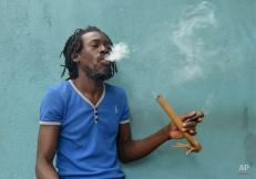A Jamaican Rastafarian known as Nature smokes marijuana for spiritual purposes outside the Trench Town Culture Yard Museum in downtown Kingston, Jamaica, Wednesday, April 15, 2015, where he works as a tour guide. Drug law amendments decriminalizing small amounts of pot and paving the way for a lawful medical marijuana sector came into effect Wednesday in Jamaica. (AP Photo/David McFadden)