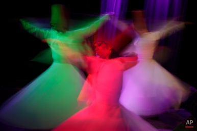 """Egyptian dancers in traditional costumes perform Sufi dance known as """"whirling dervish."""" in Cairo, Egypt, Thursday, April 23, 2015. Whirling dervishes of al-Tannura entertain visitors with their colorful and artistic spinning dance. (AP Photo/Amr Nabil)"""