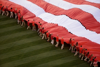 Volunteers unfurl a large American flag on the field before a baseball game between the Los Angeles Angels and the Kansas City Royals, Friday, April 10, 2015, in Anaheim, Calif. (AP Photo/Jae C. Hong)