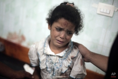 A Palestinian girl cries while receiving treatment for her injuries caused by an Israeli strike at a U.N. school in Jebaliya refugee camp, at the Kamal Adwan hospital in Beit Lahiya, northern Gaza Strip, July 30, 2014. (AP Photo/Khalil Hamra)
