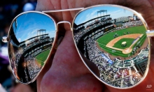 Coors Field is reflected in the sunglasses of a fan before a baseball game between the Colorado Rockies and the Chicago Cubs, Friday, April 10, 2015, in Denver. (AP Photo/Jack Dempsey)