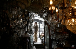A junk dealer talks on the phone outside his shop in Catania, Italy, March 25, 2015. (AP Photo/Luca Bruno)