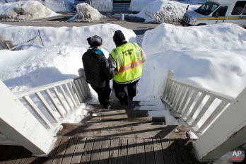 In this Tuesday March 3, 2015 photograph, Charla Nash grabs the arm of shuttle driver Roland Copeland as they walk from her front steps past five-foot high snowbanks toward a van outside her apartment in Boston. (AP Photo/Charles Krupa)