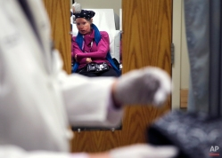 In this Tuesday March 3, 2015 photograph, Dr. Stefan Tullius, the Chief of Transplant Surgery at the Brigham and Women's Hospital, examines Charla Nash during an appointment at the hospital in Boston. (AP Photo/Charles Krupa)