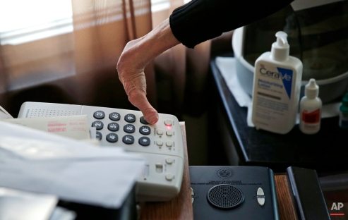 In this Friday, Feb. 20, 2015 photograph, Charla Nash checks the messages on her answering machine from a speakerphone in the bedroom at her second-story apartment in Boston. (AP Photo/Charles Krupa)