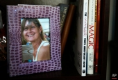 In this Friday, Feb. 20, 2015 photograph, a framed photograph of Charla Nash, taken before she was attacked by a chimpanzee, sits on a bookshelf at her second-story apartment in Boston. (AP Photo/Charles Krupa)