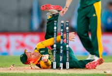 South Africa's AB de Villiers falls over as he attempts a run out during their Cricket World Cup semifinal against New Zealand in Auckland, New Zealand, Tuesday, March 24, 2015. (AP Photo/David Rowland)