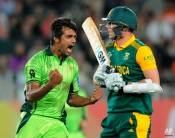 Pakistan bowler Rahat Ali, left, celebrates after taking the wicket of South Africa's Kyle Abbott, right, during their Cricket World Cup Pool B match in Auckland, New Zealand, Saturday, March 7, 2015. (AP Photo/Ross Setford)