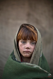 In this Friday, Jan. 24, 2014 photo, Afghan refugee girl, laiba Hazrat, 6, poses for a picture, while playing with other children in a slum on the outskirts of Islamabad, Pakistan. (AP Photo/Muhammed Muheisen)