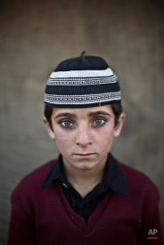 In this Friday, Jan. 24, 2014 photo, Afghan refugee boy, Hayat Khan, 8, poses for a picture, while playing with other children in a slum on the outskirts of Islamabad, Pakistan. (AP Photo/Muhammed Muheisen)