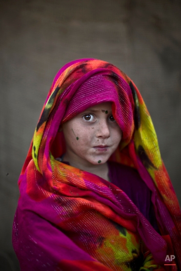 In this Friday, Jan. 24, 2014 photo, Afghan refugee girl, Robina Haseeb, 5, poses for a picture, while playing with other children in a slum on the outskirts of Islamabad, Pakistan. (AP Photo/Muhammed Muheisen)