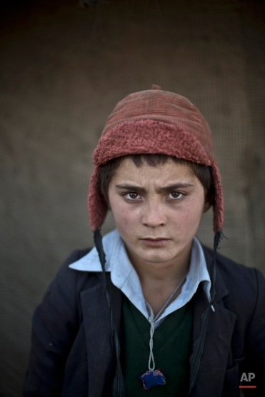 In this Friday, Jan. 24, 2014 photo, Afghan refugee boy, Awal Gul, 12, poses for a picture, while playing with other children in a slum on the outskirts of Islamabad, Pakistan. (AP Photo/Muhammed Muheisen)