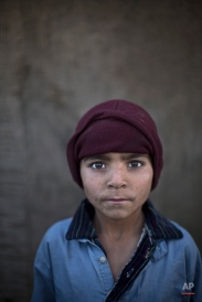 In this Sunday, Jan. 26, 2014 photo, Afghan refugee boy, Noorkhan Zahir, 6, poses for a picture, while playing with other children in a slum on the outskirts of Islamabad, Pakistan. (AP Photo/Muhammed Muheisen)