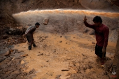 """In this May 3, 2014 photo, a jet stream of water passes above two miners known as """"Maraqueros"""" who remove stones and chunks of tree trunks that have been released with the aid of a rustic type of hydraulic jet known locally as a """"Chupadera,"""" in La Pampa in Peru's Madre de Dios region. The Chupadera aims powerful jet streams of water at earth walls, releasing the soils that hold the sought after flecks of gold. (AP Photo/Rodrigo Abd)"""
