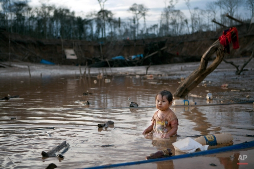 In this May 3, 2014 photo, Prisaida, 2, sits in the shallow waters of a polluted lagoon as her parents mine for gold nearby, in La Pampa in Peru's Madre de Dios region. The lagoon emerged as a result of miners bombarding the earth with jet streams of water in search of gold. (AP Photo/Rodrigo Abd)