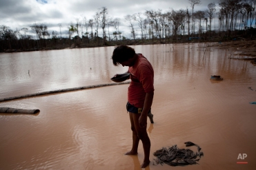 In this May 3, 2014 photo, a miner roughly estimates his handful of gold he mined, after working for over 24-hours, in La Pampa in Peru's Madre de Dios region. (AP Photo/Rodrigo Abd)