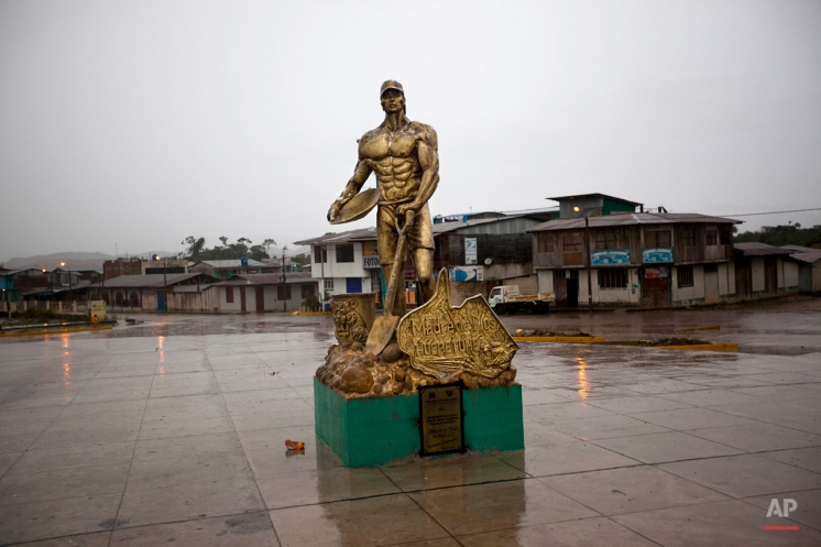 In this May 20, 2014 photo, a golden statue of a miner holding a shovel and plate stands in the empty central square of Huepetuhe in the Madre de Dios region of Peru. Thousands of people have left the Peruvian Amazon boomtown since the government halted gasoline shipments in and sent troops to destroy heavy machinery used in mining that it deemed illegal. (AP Photo/Rodrigo Abd)