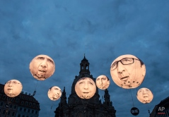 Activists of the international campaigning and advocacy organization ONE install illuminated balloons with portraits of the G7 heads of state in front of the Frauenkirche cathedral (Church of Our Lady) prior the G7 Finance Ministers meeting in Dresden, eastern Germany, Wednesday, May 27, 2015. The G7 Finance Ministers meeting is to be held in Dresden from May 27 to May 29, 2015. (AP Photo/Jens Meyer)
