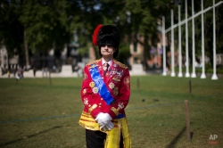 A man dressed up in his version of a ceremonial British military outfit waits for a parade and carriage procession escorting Britain's Queen Elizabeth II to arrive, at the Houses of Parliament from Buckingham Palace in London, Wednesday, May 27, 2015. The Queen will deliver a speech to open Britain's Parliament after the new Conservative government was elected. (AP Photo/Matt Dunham)