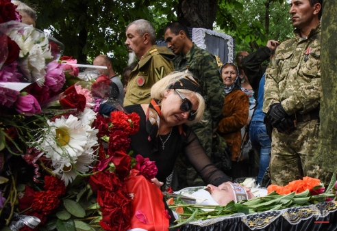 Family members mourn at a coffin with the body of prominent separatist commander Alexei Mozgovoi during his funeral in Alchevsk, Ukraine, Wednesday May 27, 2015. Alexei Mozgovoi and at least six other people were killed on Saturday in eastern Ukraine when his vehicle was ripped apart by a bomb and then strafed by gunfire. (AP Photo/Mstyslav Chernov)