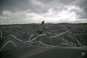U.S paratrooper of the 4th Infantry Brigade, Combat team (Airborne) 25th Infantry Division, part of the NATO-led peacekeeping mission in Kosovo serving as NATO peacekeepers in Kosovo packs his parachute after jumping from a Hercules C-130 in a military exercise near the village of Ramjan on Wednesday, May 27, 2015. U.S Army peacekeeping force regularly conducts parachute exercises to maintain proficiency in airborne operations on this deployment in Kosovo. (AP Photo/Visar Kryeziu)