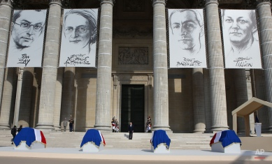 French President Francois Hollande, center, stands in front of the coffins of French resistance figures Pierre Brossolette, Germaine Tillion, Genevieve de Gaulle-Anthonioz and Jean Zay for a ceremony at the Pantheon in Paris, Wednesday May 27, 2015. The national ceremony is honoring the two women and two men, meant to symbolize French efforts against extremist violence in the past and today, four months after deadly terrorist attacks. (AP Photo/Remy de la Mauviniere/pool)
