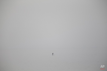 A man paddles on a board as haze and sand cover in the Mediterranean sea off Tel Aviv, Israel, Wednesday, May 27, 2015. Temperatures are soaring across the Middle East with temperatures reaching about 42 degrees Celsius (107.6 degrees Fahrenheit) in Tel Aviv. (AP Photo/Ariel Schalit)