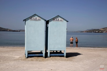 Elderly bathers chat near the sea in the industrial area of Elefsina west of Athens, on Tuesday, May 26, 2015. Greece's finance minister insisted Tuesday that the cash-strapped country will soon reach an agreement with bailout creditors, that will enable it to make a debt payment to the International Monetary Fund on June 5, which it would be otherwise unable to pay. (AP Photo/Petros Giannakouris)