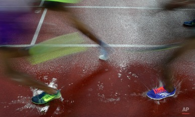 Athletes run through a puddle of water during the 5000 meters men event at the Golden Spike Athletic meeting in Ostrava, Czech Republic, Tuesday, May 26, 2015. (AP Photo/Petr David Josek)