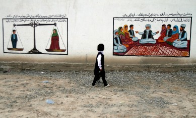 An Afghan girl walks past murals on a road in Kabul, Afghanistan, Monday, May 4, 2015. The mural on the right espouses the idea that male and female citizens have equal rights under Afghan law. The other deals with marriage issues and claims that there are no forced marriages in Islam. (AP Photo/Allauddin Khan)
