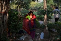 An Indian Hindu woman ties a thread around a banyan tree to seek prosperity and longevity for her husband on Somvati Amavasya in New Delhi, India, Monday, May 18, 2015. Somvati Amavasya is the no moon day that falls on a Monday in a traditional Hindu lunar calendar. (AP Photo/Tsering Topgyal)