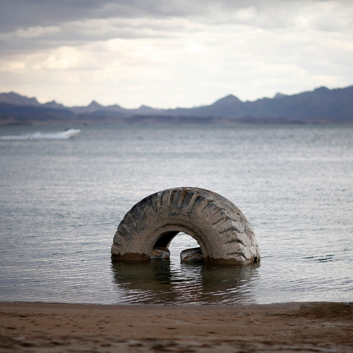 A partially submerged tire sits along the shore of Lake Mead in the Lake Mead National Recreation Area, Monday, May 18, 2015, near Boulder City, Nev. Federal water managers are projecting Lake Mead will drop to levels in January 2017 that could force supply cuts to Arizona and Nevada. (AP Photo/John Locher)