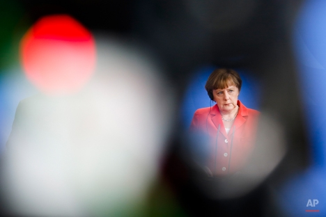 In this photo taken through a gap of a television camera with the red control light in foreground German Chancellor Angela Merkel addresses a news conference after a meeting with French President Francois Hollande at the chancellery, in Berlin, Germany, Tuesday, May 19, 2015. (AP Photo/Markus Schreiber)