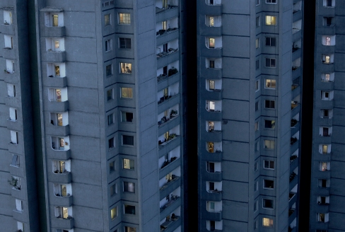 Lights are switched on in occupied apartments as dusk descends in Pyongyang, North Korea on Sunday, May 10, 2015. Majority of North Koreans live in high-rise apartments in Pyongyang. (AP Photo/Wong Maye-E)