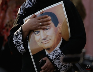 A supporter of Egypt's deposed longtime autocrat Hosni Mubarak holds his poster as she attends a celebration of his 87th birthday outside the Maadi Military Hospital, where he is hospitalized in Cairo, Egypt, Monday, May 4, 2015. The crowd gathered Monday held up photos of Mubarak and praised him with slogans of support, days before an expected May 9 verdict in his retrial on corruption charges. (AP Photo/Amr Nabil)
